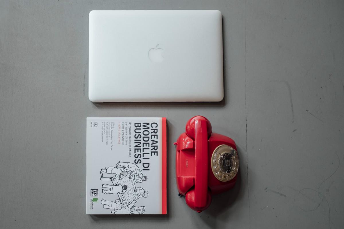 Un Mac, un telefono vintage e un libro